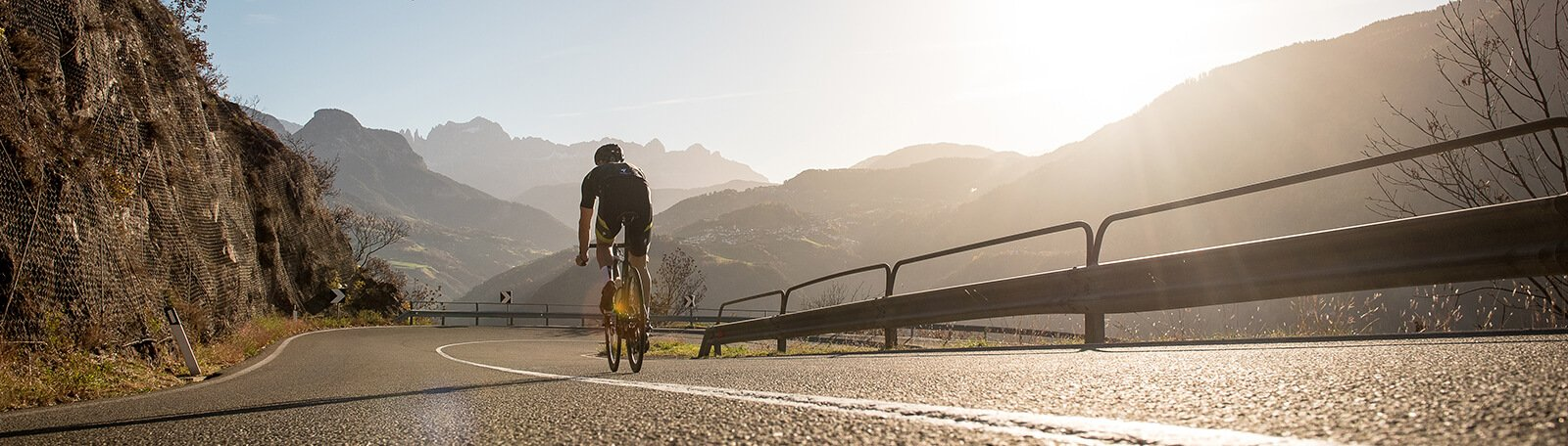 Man cycling on a road in the mountains